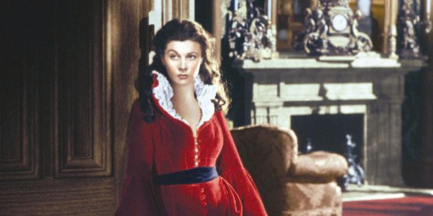 Vivien Leigh (1913-1967), British actress, wearing a long red dress trimmed with white lace, with a black...