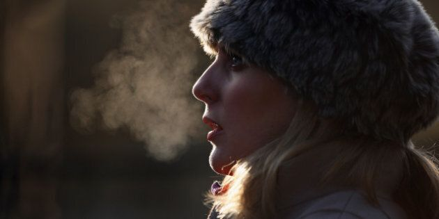 LONDON, ENGLAND - DECEMBER 12: A woman's breath is backlit on a freezing morning in Regents Park on December...
