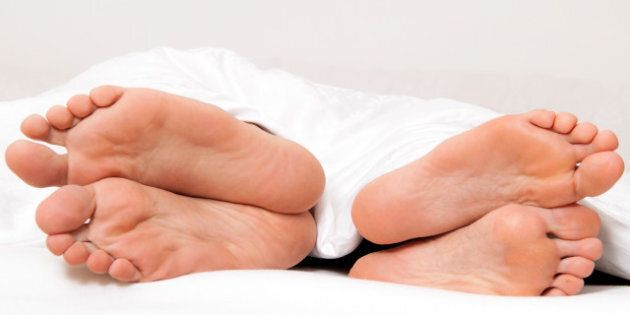 Dier feet of couple in bed. Separation and