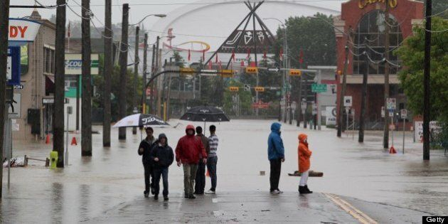Residents stand near rising waters before the Olympic Saddledome (background) in Calgary, Alberta, Canada, June 21, 2013. Flooding forced the evacuation on Friday of some 100,000 people in the western city of Calgary and nearby towns in the heart of the Canadian oil patch. AFP PHOTO / DAVE BUSTON (Photo credit should read DAVE BUSTON/AFP/Getty Images)