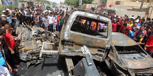Iraqis gather around burnt vehicles at the site of a car bombing at a market in Baghdad's impoverished...