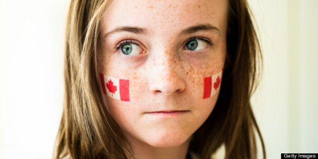 Girl with wide blue eyes and freckles, wearing Canadian flag on temporary tattoo on her cheeks.