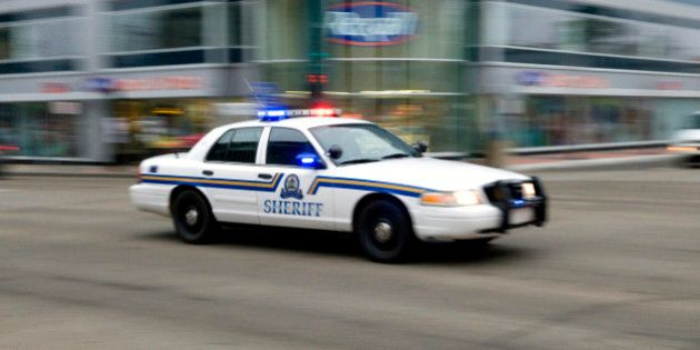 EDMONTON, CANADA - OCTOBER 21: A sheriff's car speeds through the downtown streets on its way to a hostage...