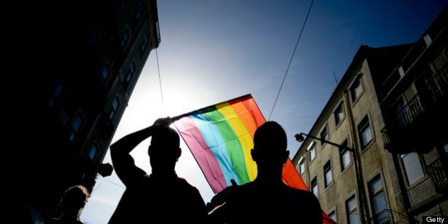 A man waves a rainbow flag as he takes part in the Gay Pride Parade in Lisbon on June 22, 2013. AFP PHOTO/...