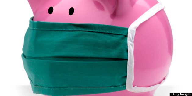 Pink piggy bank wearing a surgical mask to protect from