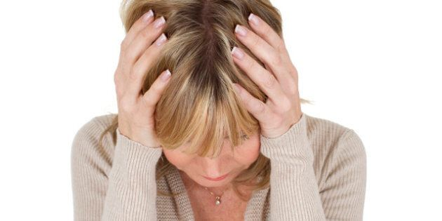 mature woman with her head in her hands as depression concept isolated on white