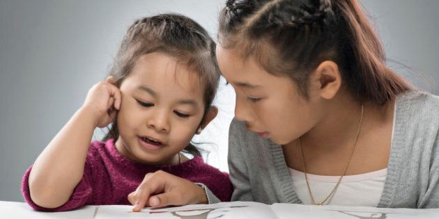 two sisters reading a picture book