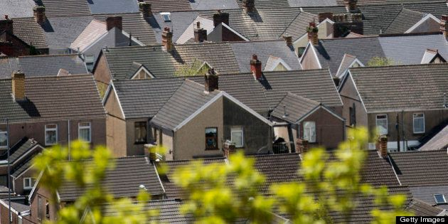 The tiled roof tops of homes in a housing estate are seen near the steel works operated by Tata Steel...