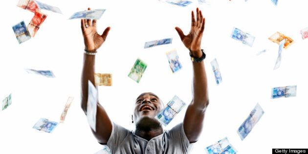 A happy man looks up smiling as he tries to catch hundreds of falling banknotes. The banknotes are varied...