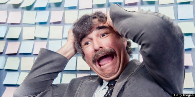 This is a horizontal, color photograph of an older mustached man sitting in front of a cubicle wall that is covered with sticky notes. He pulls at his hair and screams in frustration.