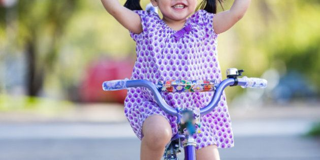 Little girl riding and smiling with her fingers held up