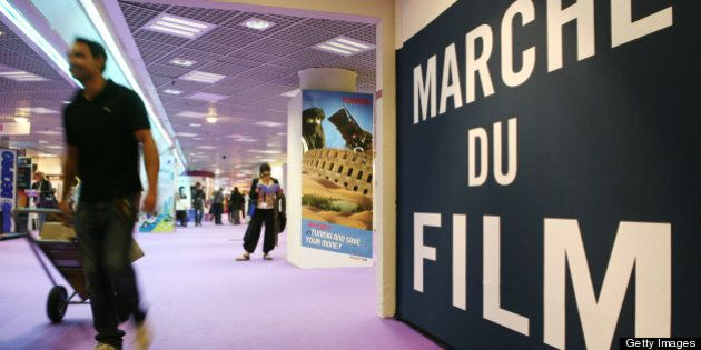 A man walks by the sign of the Marche du Film (film market) at the 63rd Cannes Film Festival on May 12,...