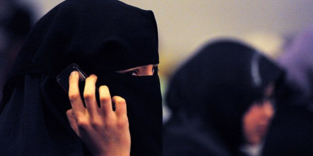 A woman wearing a burqa talks on a mobile phone during the 'Uprising in the Muslim World' Khilafah Conference...