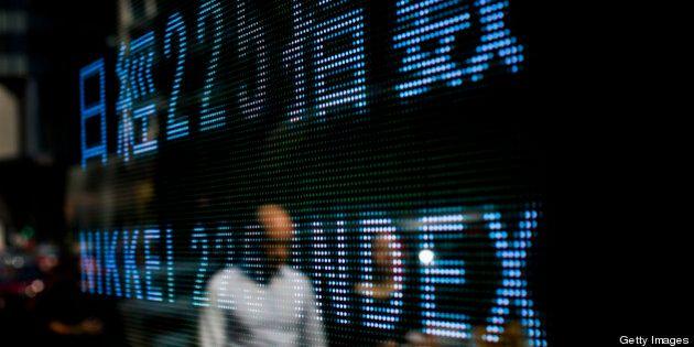 A pedestrian is reflected on an Nikkei ticker in Hong Kong, China, on Wednesday, Oct. 10, 2012. Hong...