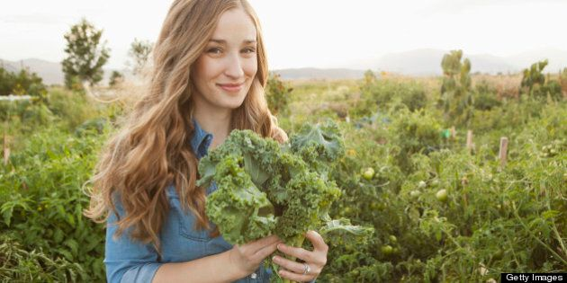 USA, Utah, Salt Lake City, Portrait of young woman holding kale