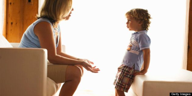 Mother discussing serious issue with child as if disciplining his behovior or teaching him a
