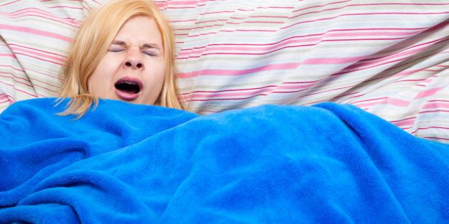 sleepy woman yawning wrapped in