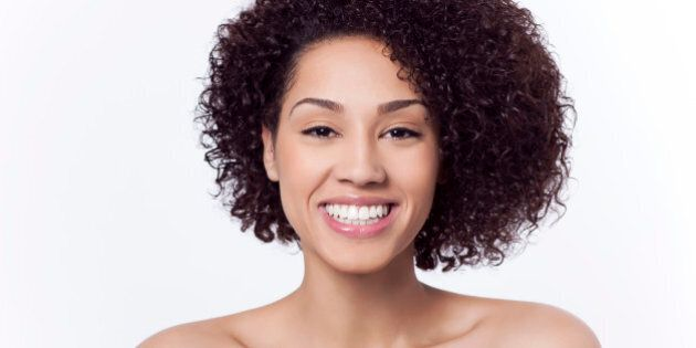 Attractive mixed race young adult woman with a beautiful face and dark brown curly hair in front of a...
