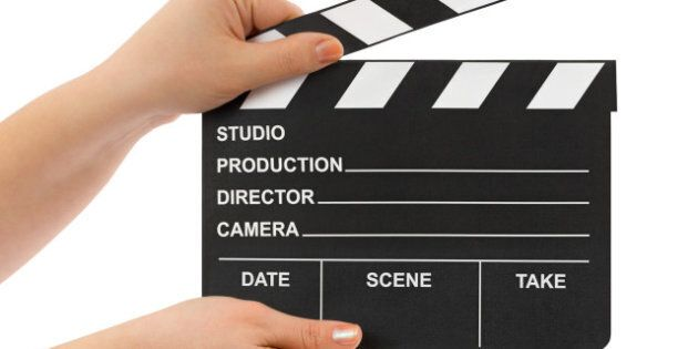 Hands with cinema clapboard isolated on white