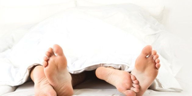 Foot of two people in the bedroom, on white