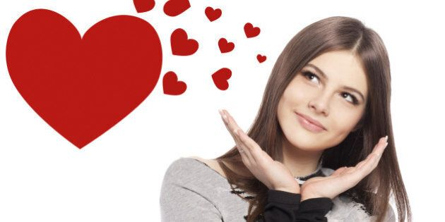 Valentines Day. Beautiful girl teenager with Valentines Day heart sign glossy hair with copy space closeup in studio on white background
