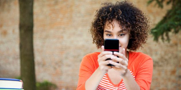Ethnic female student with curly hair wearing wearing an orange shirt and texting with her smart phone