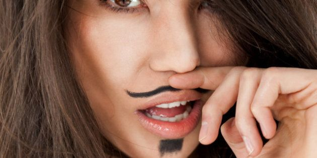Close-up of female face with moustache dendy makeup