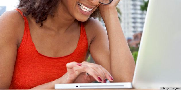 Young woman smiling working on a laptop