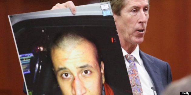 SANFORD, FL - JULY 12: Defense attorney Mark O'Mara holds up the photo of George Zimmerman from the night...