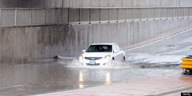 TORONTO, ON - JUNE 28: Drivers attempt to drive through flooded area on North Queen in Etobicoke. (Vince...