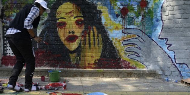 Indian artists create wall paintings during the 'Design The Change' wall art event in New Delhi on February 24, 2013.  The activity brought together more than 500 professional and budding artists on the same platform to create the wall art. Artists used their imagination and creativity to give justice to the theme and depicted the essence of transformation needed for the betterment of society.  AFP PHOTO/SAJJAD HUSSAIN        (Photo credit should read SAJJAD HUSSAIN/AFP/Getty Images)