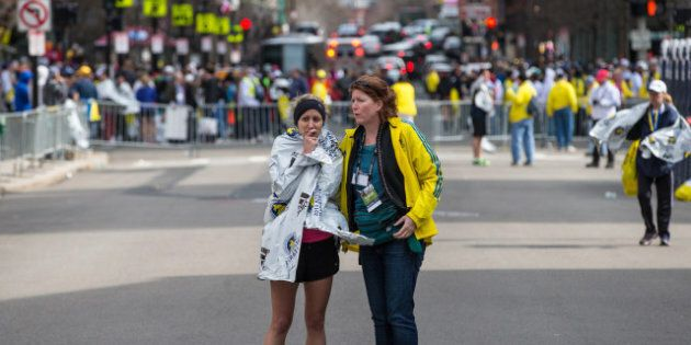 BOSTON - APRIL 15: A runner was comforted following two explosions on Boylston Street in Boston near the finish line of the Boston Marathon. (Photo by Aram Boghosian for The Boston Globe via Getty Images)