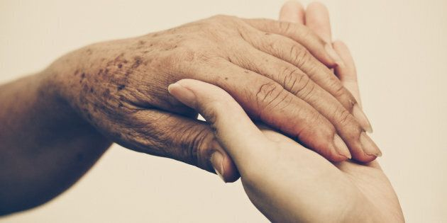 Young female hand holding old female hand - Taking care of the elderly people with