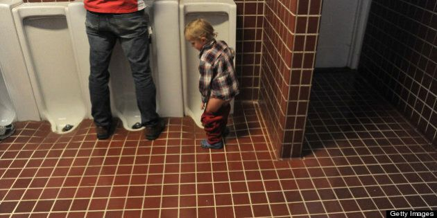 Boy pulls up pants after using the urinal in tiled