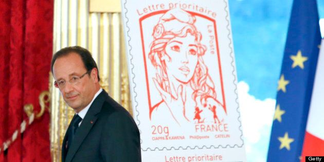 French President Francois Hollande walks past the new official Marianne, the symbol of the French republic,...