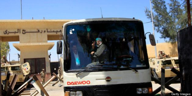 Palestinian men gesture from inside a bus as they cross back into the southern Gaza Strip through the...