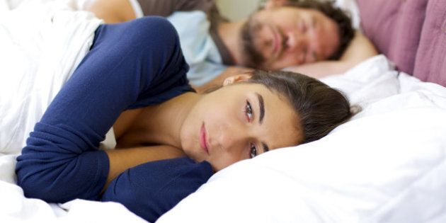 Depressed woman in bed while husband is sleeping not caring about