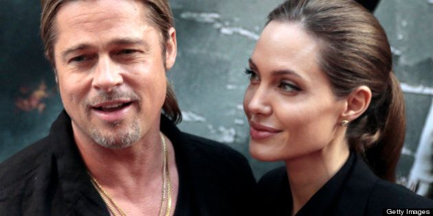 US actors Brad Pitt (L) and Angelina Jolie arrive for the premiere of 'World War Z' on the Champs Elysees Avenue in Paris on June 3, 2013. AFP PHOTO / JACQUES DEMARTHON (Photo credit should read Demarthon/AFP/Getty Images)