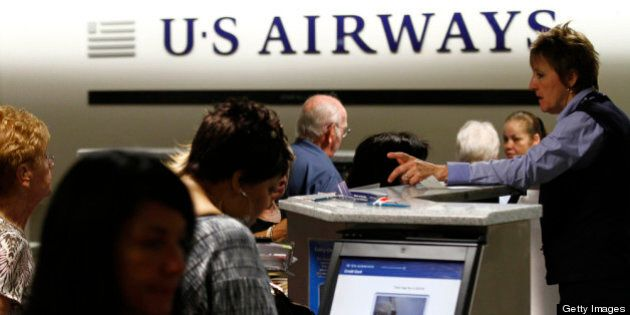 PHOENIX, AZ - APRIL 19: Travelers check-in at the US Airways ticket counter at Sky Harbor International Airport on April 19, 2012 in Phoenix, Arizona. As American Airlines continues through bankruptcy US Airways is working on a possible deal to takeover the troubled airline.  (Photo by Joshua Lott/Getty Images)
