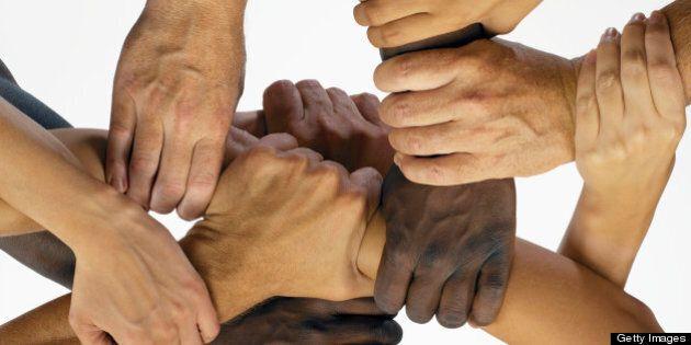 Men and women interlocking hands, close-up, overhead