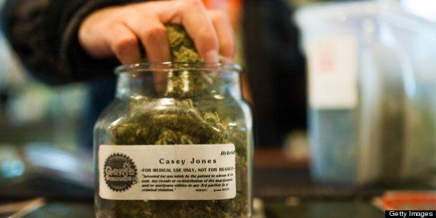 An employee of Ganja Gourmet in Denver, Colorado, re-stocks 'top shelf' medical marijuana in the business's...