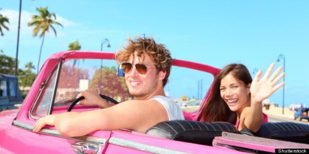 Couple happy in vintage retro convertible car. Friends driving on summer road trip in pink car. Beautiful...