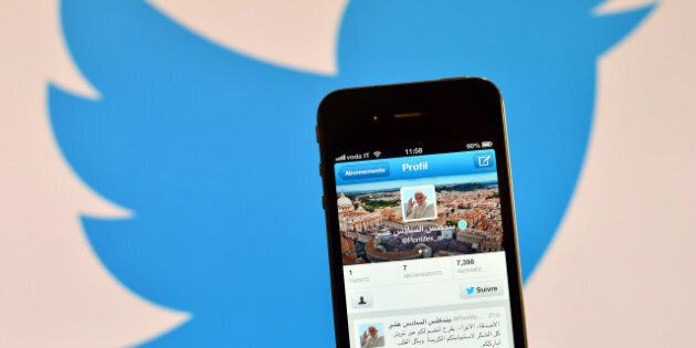 A smartphone showing the first twitter message of Pope Benedict XVI in Arabic is held in front of a computer...