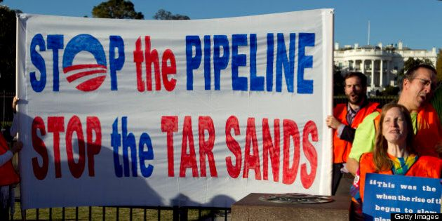 Demonstrators hold a sign near the White House during a Keystone XL tar sands oil pipeline demonstration...
