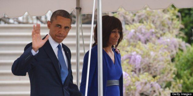 US President Barack Obama and First Lady Michelle Obama make their way across the South Lawn to board...