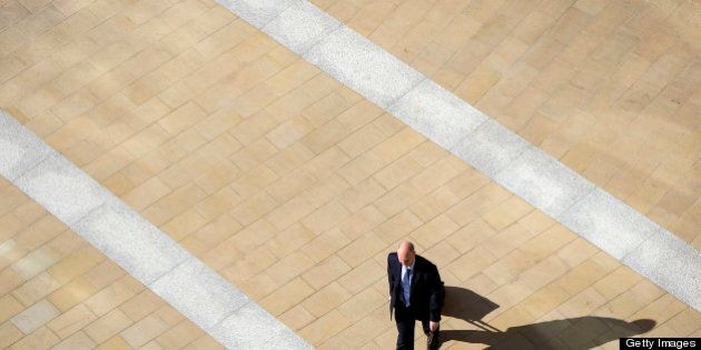 A businessman walks away from the London Stock Exchange and across Paternoster Square in London, U.K., on Tuesday, April 23, 2013. The pound rose for a third day against the euro before an industry report that economists said will show U.K. retail sales increased and amid speculation the Bank of England's loan-program extension will boost the economy. Photographer: Simon Dawson/Bloomberg via Getty Images