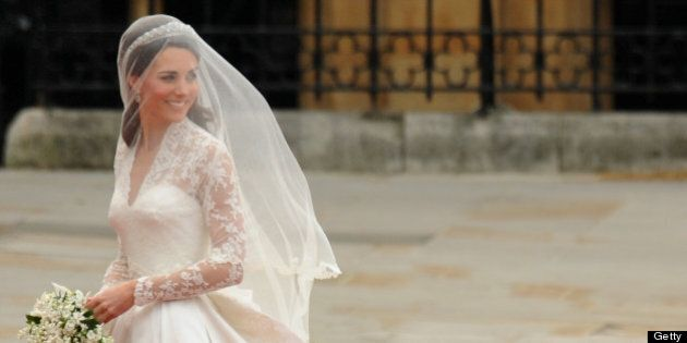 Kate Middleton smiles as she arrives at the West Door of Westminster Abbey in London for her wedding...