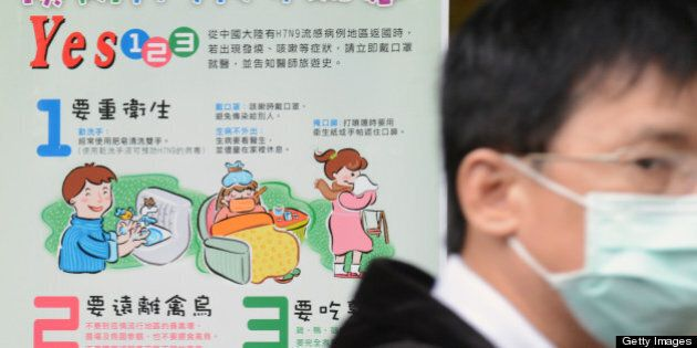 A man wearing a mask walks past a H7N9 poster outside the National Taiwan University Hospital in Taipei...