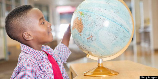 Excited little boy studying map in elementary