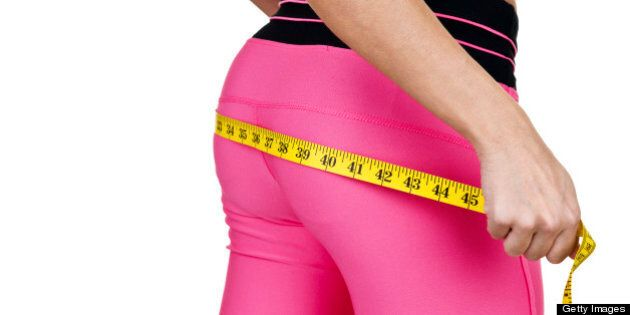 Woman wearing fitness clothing measuring her buttocks for a fitness and weight loss